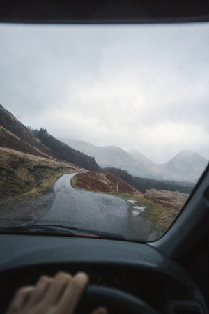 Man driving a car in the Highlands, Scotland Stock Photo