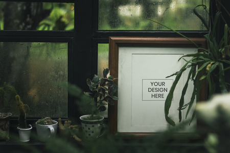 Blank photo frame with houseplants by the window