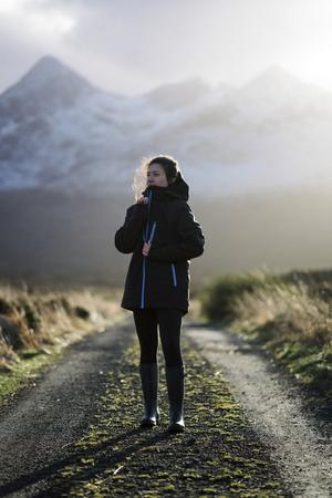 Woman on a road in Glen Etive, Scotland Standard-Bild