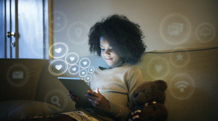 Young black kid using a digital tablet before bedtime