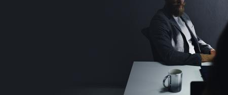 Casual businessman sitting in the dark Archivio Fotografico