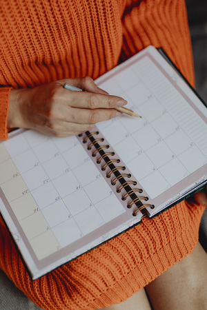 Woman writing on her daily planner