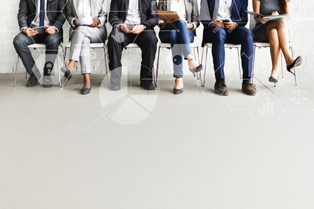 Group of diverse people sitting in a line on chairs