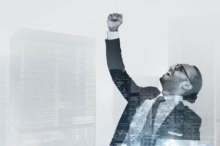 Odnoszący sukcesy biznesmen podnoszący rękę w powietrzu