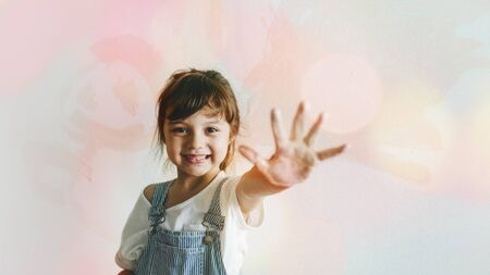 Cheerful girl with a hand covered in paint