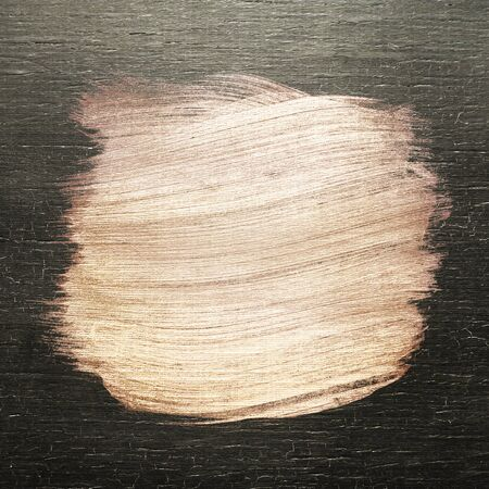 Rose gold oil paint brush stroke texture on a colored wood background