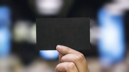 Hand holding a black paper card website banner template Stock Photo
