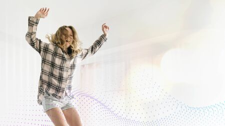 Woman jumping with joy on her bed Stock Photo