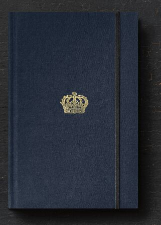 Baroque style crown on a navy blue notebook