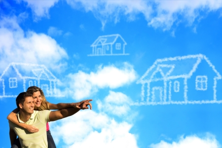 couple home: Happy couple under the blue sky enjoying the sun pointing to a house made of clouds.