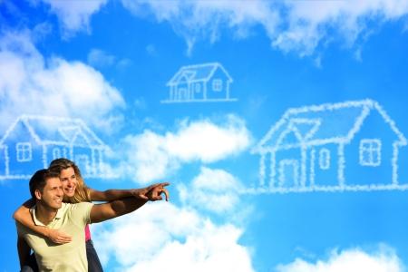 pareja en casa: Pareja feliz bajo el cielo azul de disfrutar del sol apuntando a una casa hecha de nubes.