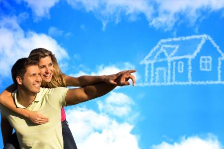 Pareja feliz bajo el cielo azul de disfrutar del sol apuntando a una casa hecha de nubes.