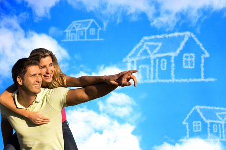 real time: Happy couple under the blue sky enjoying the sun pointing to a house made of clouds.