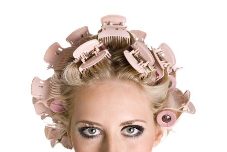Young beautiful girl is having hair curlers on her head Stock Photo