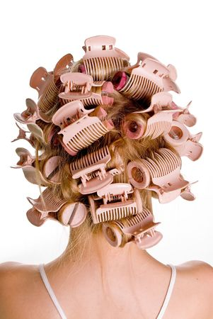 untangle: Young beautiful girl is having hair curlers on her head Stock Photo