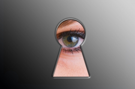 Woman looks through a keyhole photo