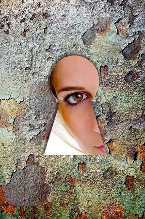 Vrouw kijkt door een sleutel gat