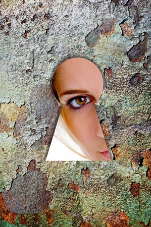 Woman looks through a keyhole photo
