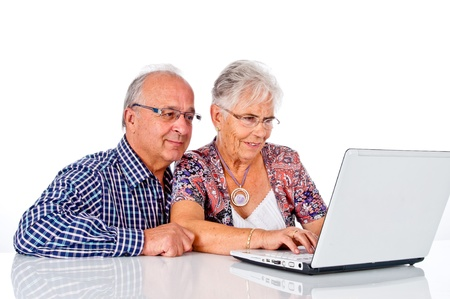 mujeres mayores: Pareja de la tercera edad en el trabajo con ordenador port�til en casa Foto de archivo