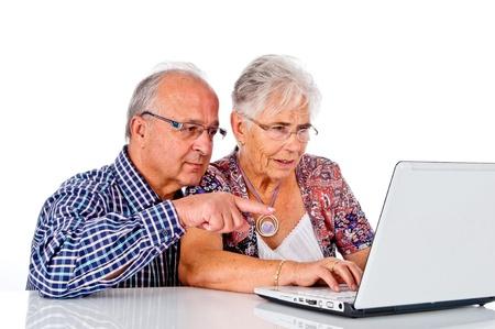 mujeres mayores: Pareja de personas mayores que trabajan con el portátil en casa Foto de archivo