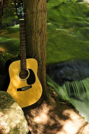 Acoustic Guitar Near Small Creek Waterfall photo