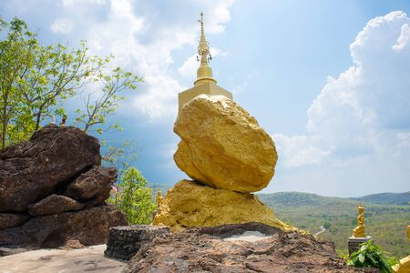 lamphun: golden pagoda on golden stone with cloud and blue sky background in Lamphun