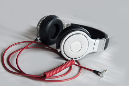 jukebox: blackred headphones on bed Stock Photo