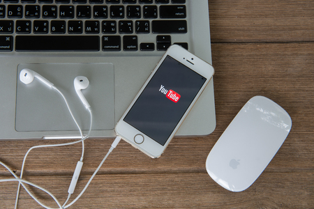 CHIANGMAI, THAILAND -June 22, 2015:Brand new Apple iPhone with YouTube app on the screen lying on desk with headphones.