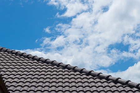 tile of roof: roof on a new house with blue sky