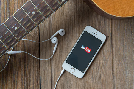 CHIANGMAI, THAILAND -June 23, 2015:Brand new Apple iPhone with YouTube app on the screen lying on desk with headphones