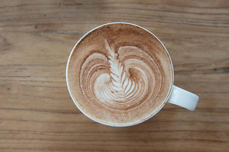 kafe: Latte art coffee over wooden background