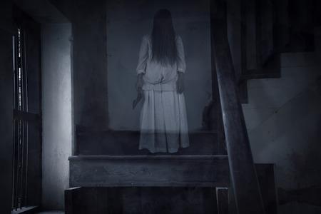 escena de una película de terror con una figura solitaria en la sala, Escena del horror de una mujer asustadiza Foto de archivo