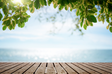 Wooden houses by the sea Wood table top with blurred nature scene tropical beach and blue sky, holiday background concept - can be used for display or montage your products. Stock Photo - 58335443