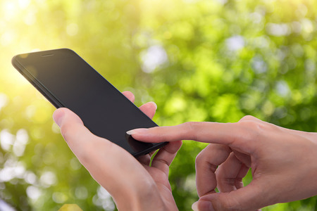 Close up of a woman using mobile smart phone outdoo,Natural Bokeh Stock Photo - 82836293