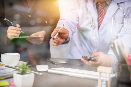 Doctor hand working smart phone Doctor explaining patient's illness and treatment time, sun flare effect photo Medical technology network team meeting concept. Reklamní fotografie