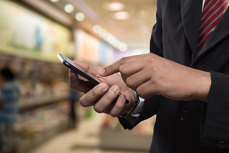 Business man in shopping mall using mobile phone.