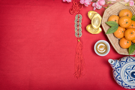 Top view accessories Chinese new year festival,leaf,wood basket,red packet,plum blossom,teapot on red background. Stock Photo
