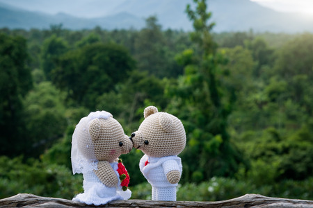 Two teddy bears in love sitting on grass Stock Photo