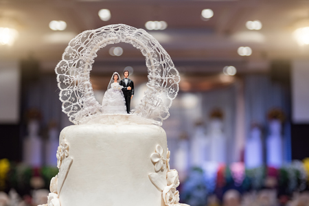 Close-up of figurine couple on wedding cake at wedding with bokeh Stock Photo