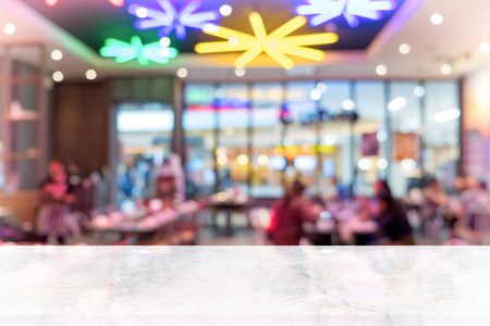 White marble table top on blur coffee shop window background. For product or foods montage.