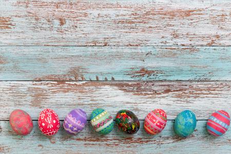 Colorful Easter egg side border against a rustic wood Vintage pastel background