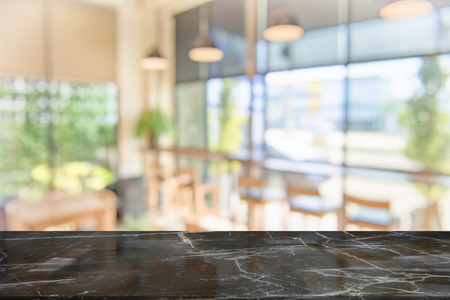 black marble table top on blur coffee shop window background. For product or foods montage.