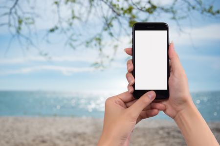 Young womanholding mobile smart phone and the background is the sea during the holiday season Stock Photo