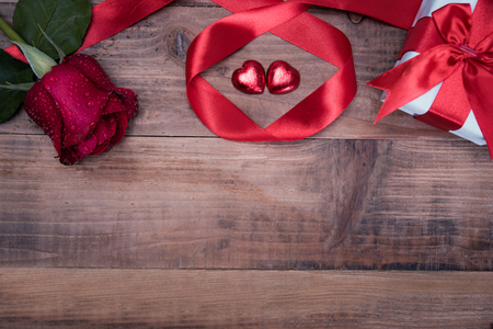 Valentines day background with rose and ribbon on wooden. Stock Photo