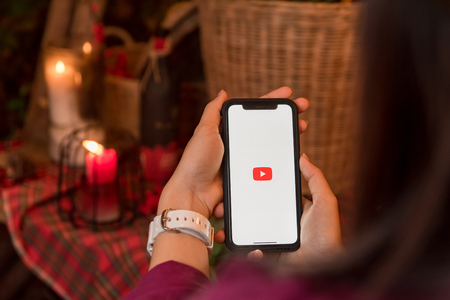 CHIANGMAI, THAILAND - JAN 16,2018 :Brand new Apple iphone X with YouTube app on the screen lying on old wood desk with headphones. YouTube is the popular online video sharing website