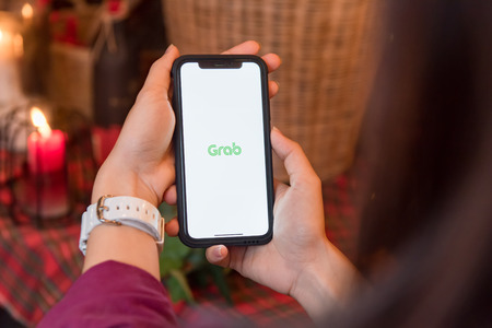 CHIANGMAI, THAILAND - FEB 12,2018 :Brand new Apple iphone X with GRAB application display on mobile screen in male hand's while he calling some Redactioneel