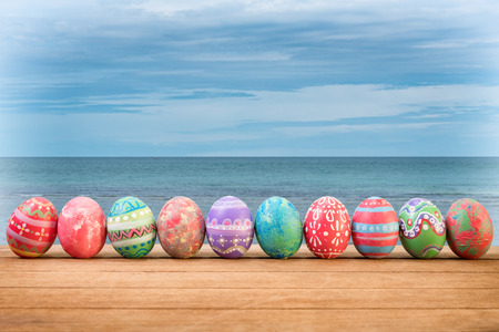 Easter Eggs Grass On the beach, the sea, beautiful summer morning.Colorful Easter egg side border against a rustic wood background