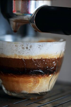 closeup of a glass cup of cappuccino and handle of the coffee maker photo