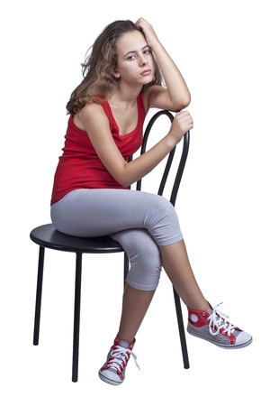 red tshirt: Young girl, with red T-shirt, sitting on a black metal chair, isolated on a white background