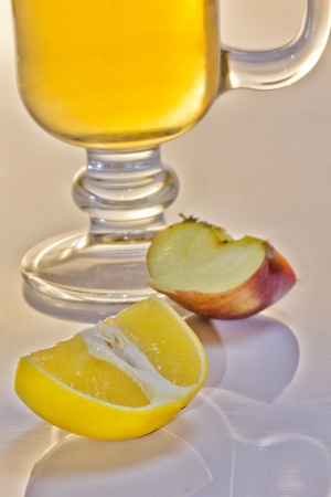 A glass cup of tea, a piece of lemon and a piece of apple, isolated on a white  photo